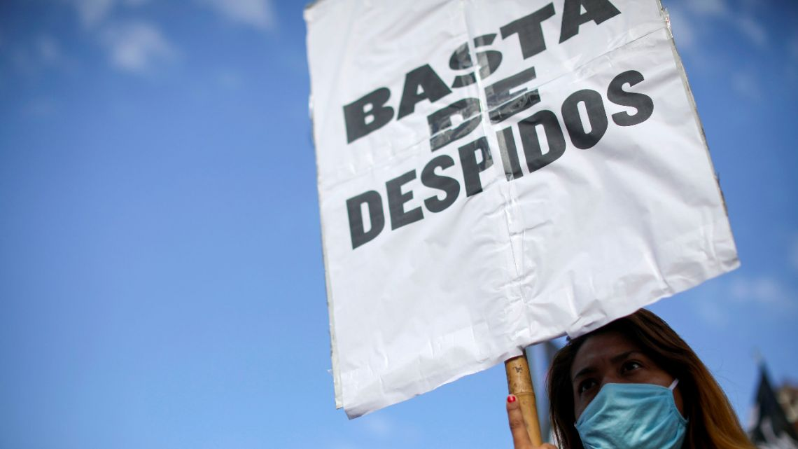 "An activist holds up the sign ""Stop the layoffs"" during a protest marking May Day, or International Workers' Day, amid a government-ordered lockdown to curb the spread of coronavirus in Buenos Aires, Friday, May 1, 2020."