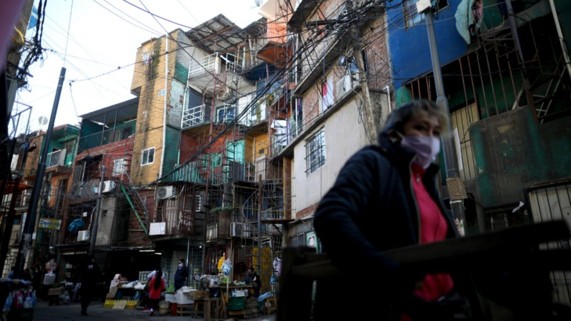 A woman, wearing protective face mask to help curb the spread of the new coronavirus, walking in Villa 31 during a government-ordered shutdown, in Buenos Aires. Thursday, April 30, 2020. According to official data, the number of confirmed cases of COVID-19 in Villa 31 have increased in the past week, putting authorities on high alert.