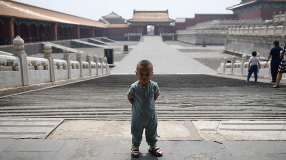 Los visitantes usan mascarillas como medida preventiva contra el Coronavirus, mientras caminan por la Ciudad Prohibida, el antiguo palacio de los emperadores de China.