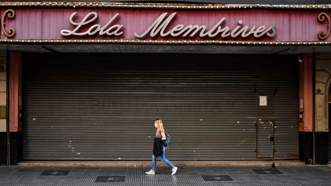 A woman wearing a face mask walks past the Lola Membrives theatre in Buenos Aires.