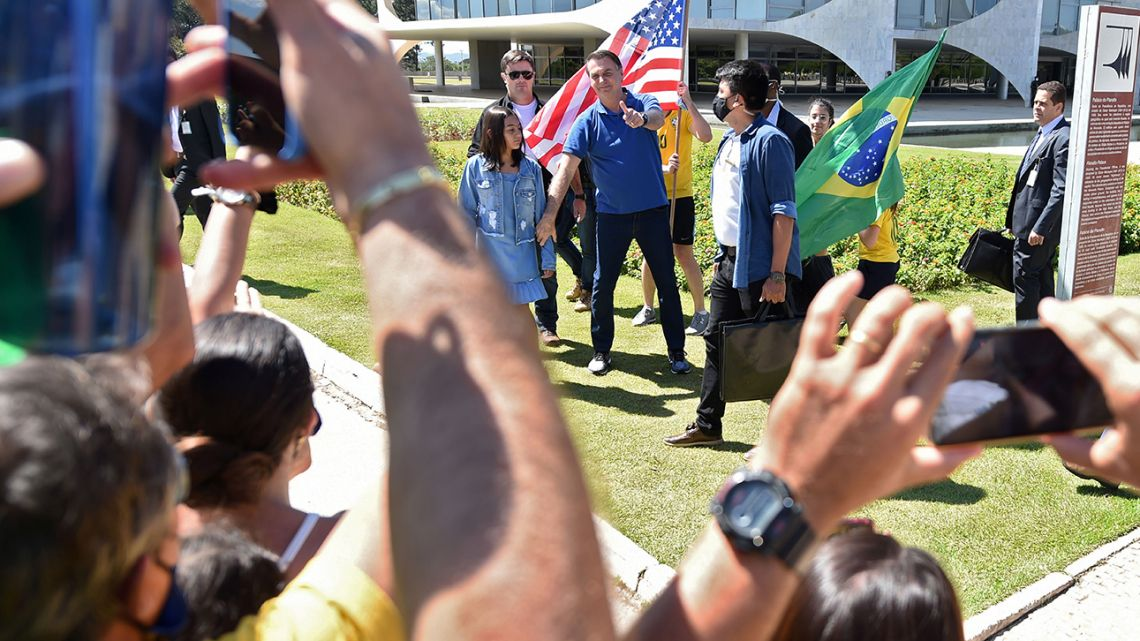 Brazilian President Jair Bolsonaro, next to his daughter Laura (left), gives a thumb up at supporters gathering outside Planalto Palace in Brasilia, on May 3, 2020.