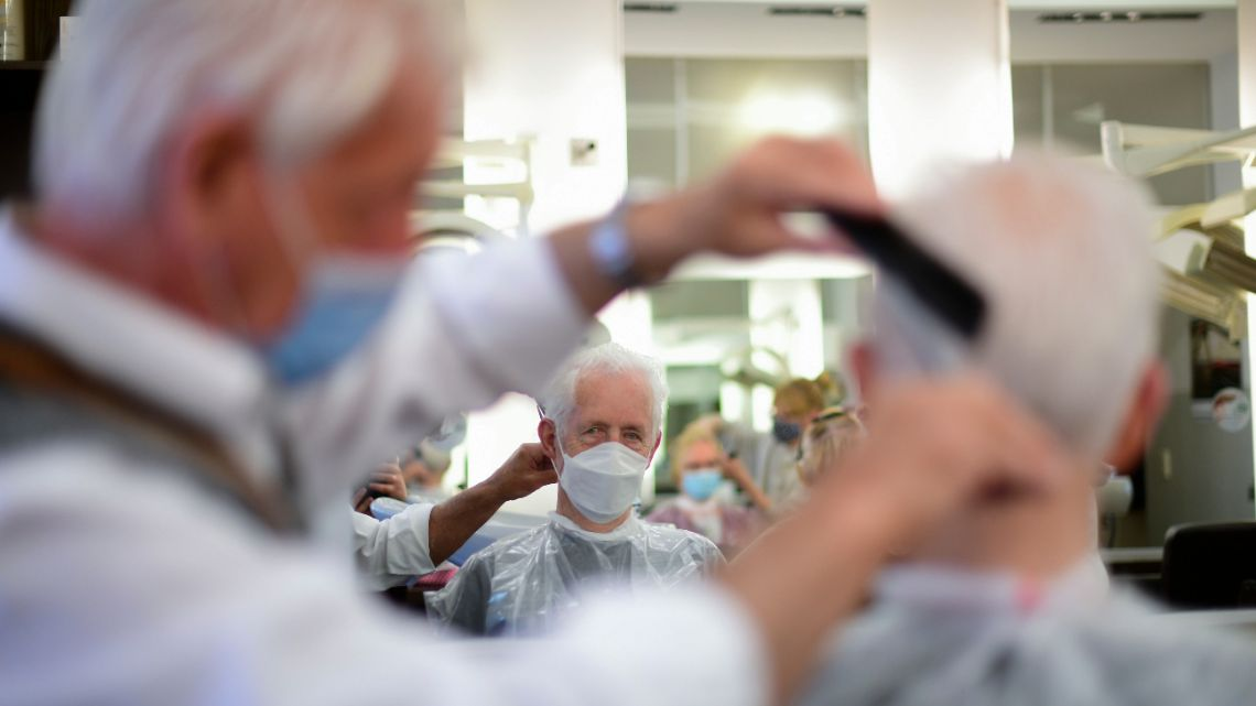Hairdresser Dieter Fiedler wears a face mask as he cuts the hair of a client at his hairdressing salon 'Fiedler' in Dortmund, western Germany, on May 4, 2020, amid the new coronavirus Covid-19 pandemic.