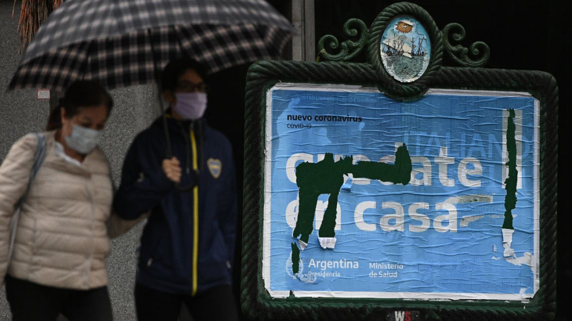 "People pass by a damaged sign which read ""Stay at Home"" in Buenos Aires, Argentina, on May 4, 2020 during the lockdown imposed by the government against the spread of the new coronavirus, COVID-19."