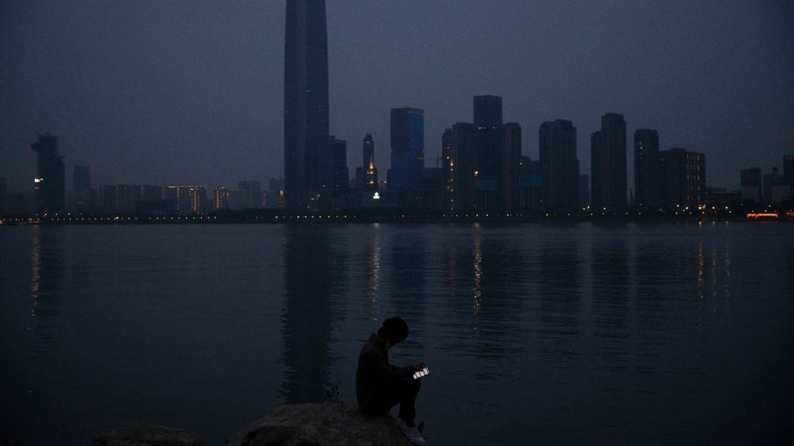 In this April 5, 2020, file photo, a man checks his mobile phone along the Yangtze River in Wuhan in central China's Hubei province.