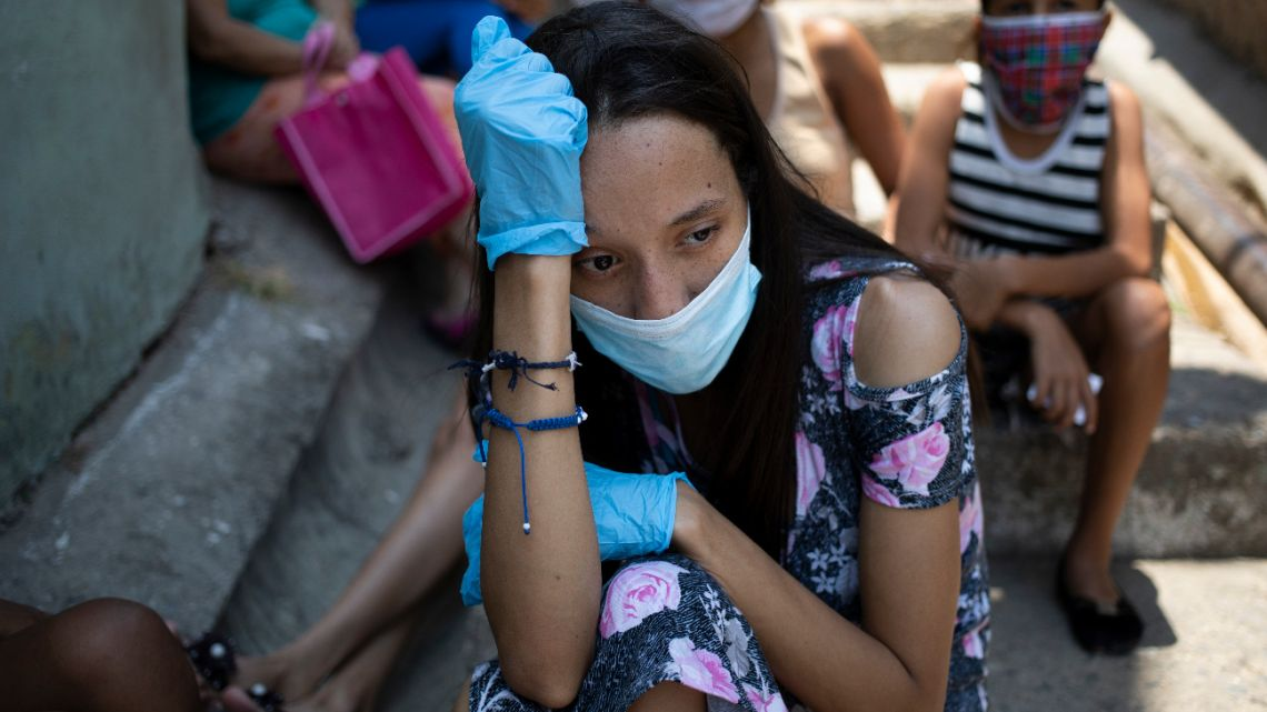 A woman wearing a mask and gloves against the spread of the new coronavirus, waits outside a soup kitchen run by nuns, waiting for it to open and get some food, in Caracas' Petare slum in Venezuela, Thursday, April 30, 2020.