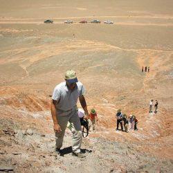 Los viajeros trepan por las rojizas laderas en busca de mejores vistas del Valle de los Colorados.