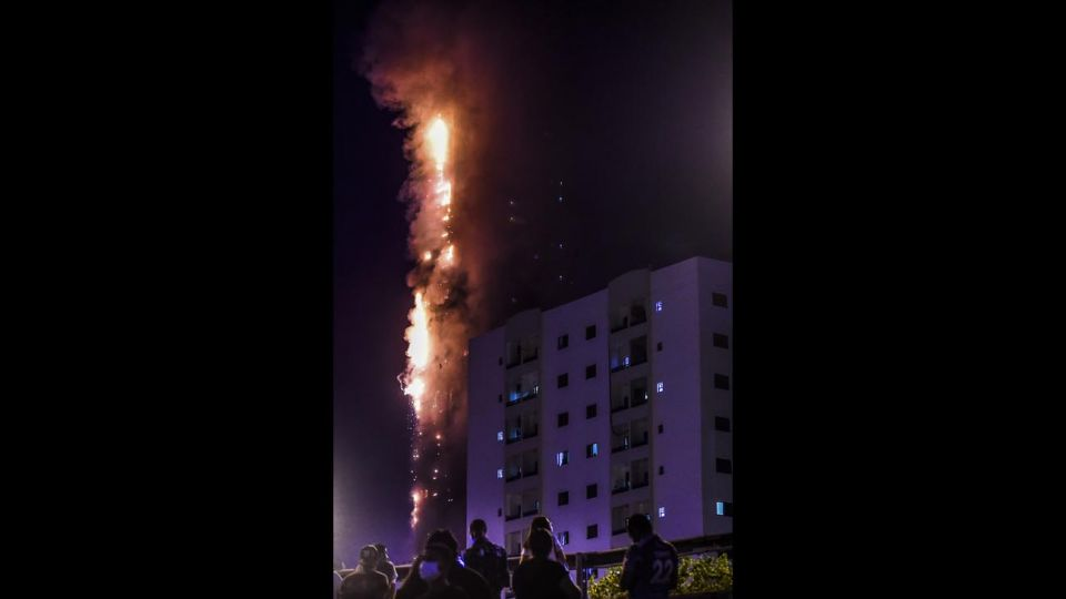 La gente se para en un puente y observa un incendio que se produce en una torre de 48 pisos en Sharjah, en los Emiratos Árabes.