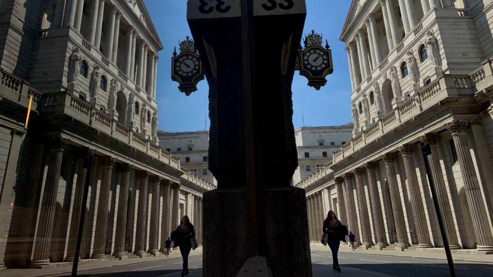 El reflejo de una ciudadana en una ventana mientras camina por el Banco de Inglaterra en Londres.