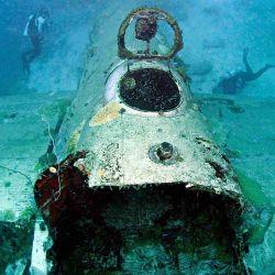 Avión oxidado en el fondo marino.