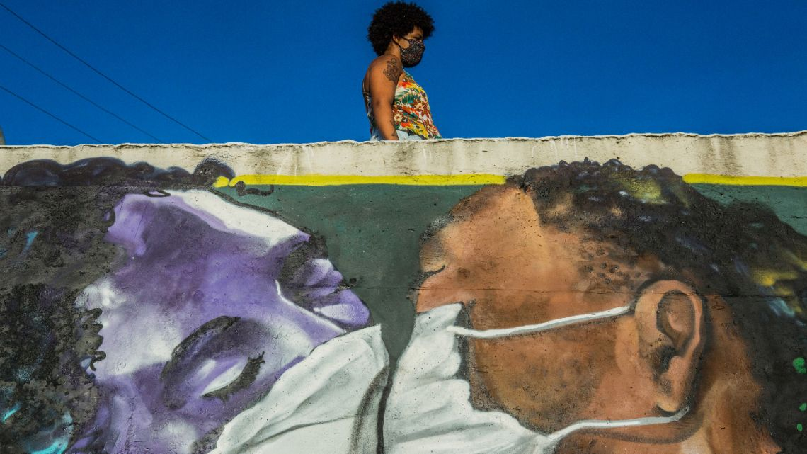 In this file photo taken on April 15, 2020 a woman wearing a face mask stands above a graffiti by Brazilian artist Marcos Costa, or Spray Cabuloso, at the entrance of the Solar de Unhao favela in Salvador, Bahia, Brazil.