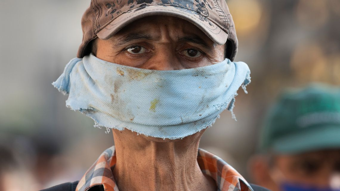 A man wears a piece of cloth as a face mask amid the spread of the new coronavirus at a street market in Caracas, Venezuela, Friday, April 10, 2020.
