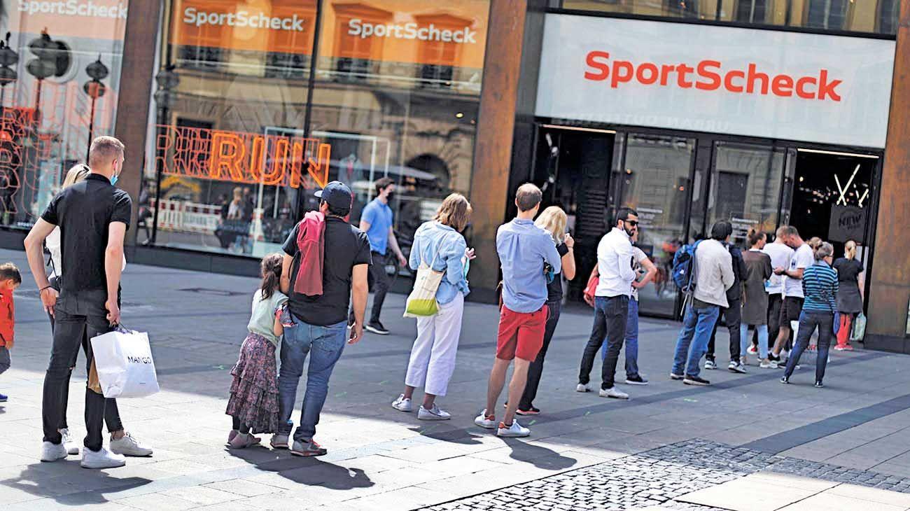 Distanciamiento social. Clientes en fila ante un local de productos deportivos en Munich.