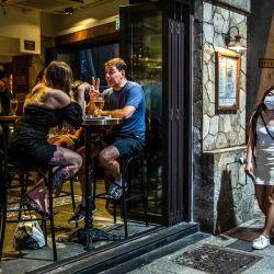 La gente se reúne para beber en un bar en Hong Kong el 9 de mayo de 2020. - Hong Kong suavizó las leyes de distanciamiento social el 8 de mayo que permitieron la apertura de algunos negocios, incluidos bares, cines y gimnasios con ciertas condiciones. (Foto por ISAAC LAWRENCE / AFP)   Foto:AFP