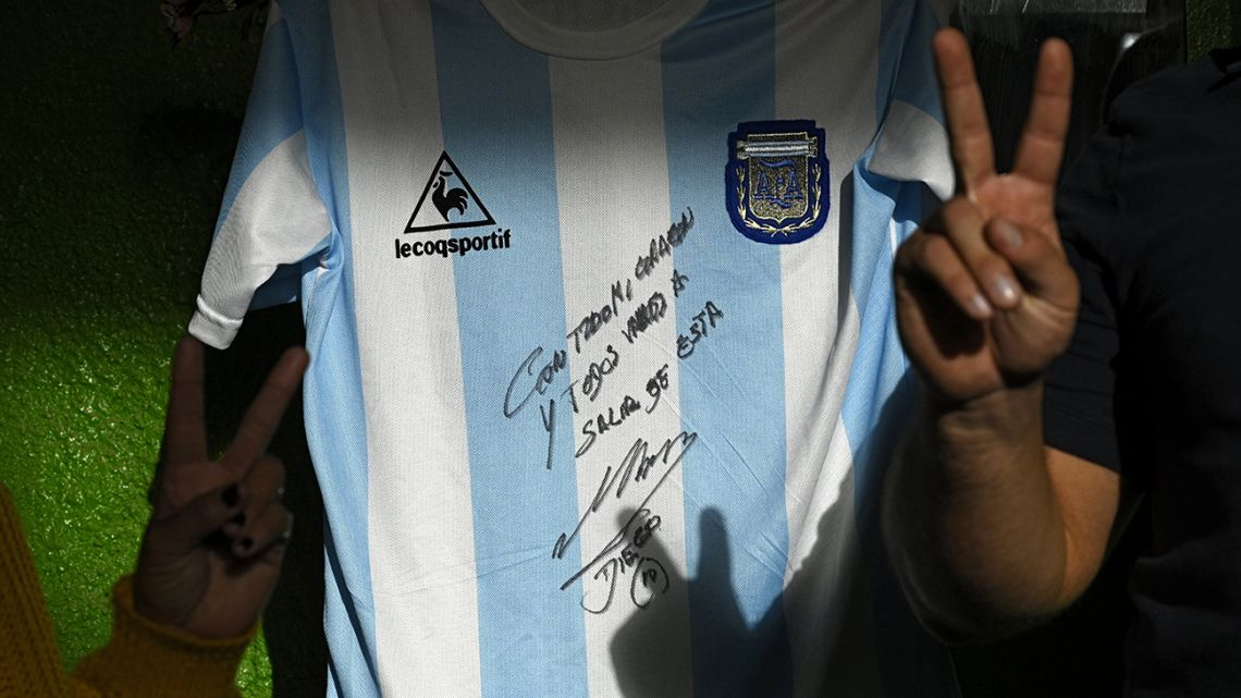 People flash the 'V' sign next to a replica of Argentina's football team jersey used during the final of the FIFA World Cup Mexico '86, handwritten and signed by Argentine former football star Diego Maradona, at a community soup kitchen in José C. Paz, Buenos Aires.