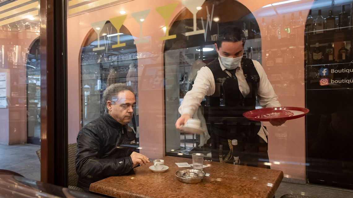 A waiter serves coffee to a guest at the restaurant Portico on the Piazza Grande in Locarno, Switzerland.