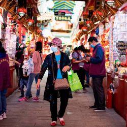Una mujer con una máscara facial camina por los puestos en Beijing el 12 de mayo de 2020. - La inflación de los consumidores de China volvió a caer en abril desde hace un año, mostraron datos oficiales el 12 de mayo, aunque los analistas advirtieron sobre un repunte posterior de la escasez de suministro causada por el coronavirus. (Foto por NOEL CELIS / AFP)   Foto:AFP