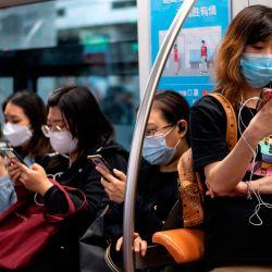 Los pasajeros que usan mascarillas usan sus teléfonos móviles en el metro de Beijing el 12 de mayo de 2020. (Foto de Noel CELIS / AFP)   Foto:AFP