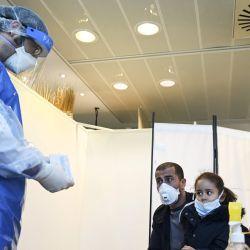Un miembro del personal médico con máscara y traje de protección, y un protector facial, se prepara para recoger de un hombre y su hija en un centro de pruebas COVID-19 establecido en el Parlamento Europeo el 12 de mayo de 2020, en Estrasburgo, este de Francia. dos días después de que Francia alivió las medidas de bloqueo tomadas para frenar la propagación de la pandemia COVID-19, causada por el nuevo coronavirus. (Foto por FREDERICK FLORIN / AFP)   Foto:AFP