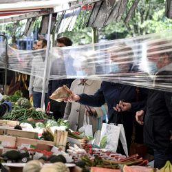 Un vendedor de frutas y verduras con una mascarilla protectora atiende a los clientes que se encuentran detrás de una protección plástica en el mercado    Foto:AFP
