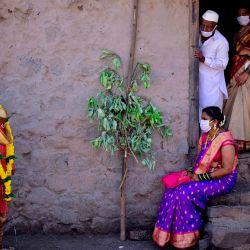 El novio Vitthal Koditkar (L) de la aldea de Hirpodi habla con su novia Vrushali Renuse (R) de la aldea de Pabe y miembros de la familia después de su boda durante un bloqueo nacional impuesto por el gobierno como medida preventiva contra el coronavirus COVID-19, en la aldea de Pabe en Pune distrito. (Foto por Sanket Wankhade / AFP)   Foto:AFP
