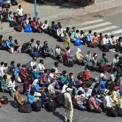 Los trabajadores migrantes abandonados hacen cola para abordar los autobuses que los llevan a una estación de ferrocarril para tomar servicios especiales de trenes para regresar a sus hogares después de que el gobierno alivió un bloqueo nacional como medida preventiva contra la propagación del coronavirus COVID-19 en Ahmedabad el 12 de mayo de 2020 (Foto por SAM PANTHAKY / AFP)   Foto:AFP