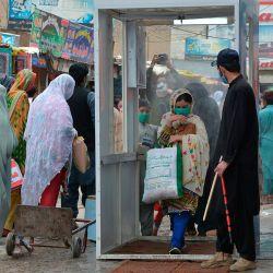 La gente camina por una puerta de desinfección en un mercado después de que el gobierno alivió un bloqueo nacional impuesto como medida preventiva contra el coronavirus COVID-19, en Quetta, el 12 de mayo de 2020. (Foto de Banaras KHAN / AFP)   Foto:AFP