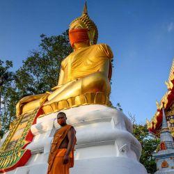 Un monje camina frente a una estatua gigante de Buda con una máscara facial en el templo Wat Nithet Rat Pradit en Pathum Thani, en las afueras de Bangkok, el 12 de mayo de 2020, mientras el país se enfrenta a la nueva situación del coronavirus COVID-19. (Foto por Mladen ANTONOV / AFP)   Foto:AFP