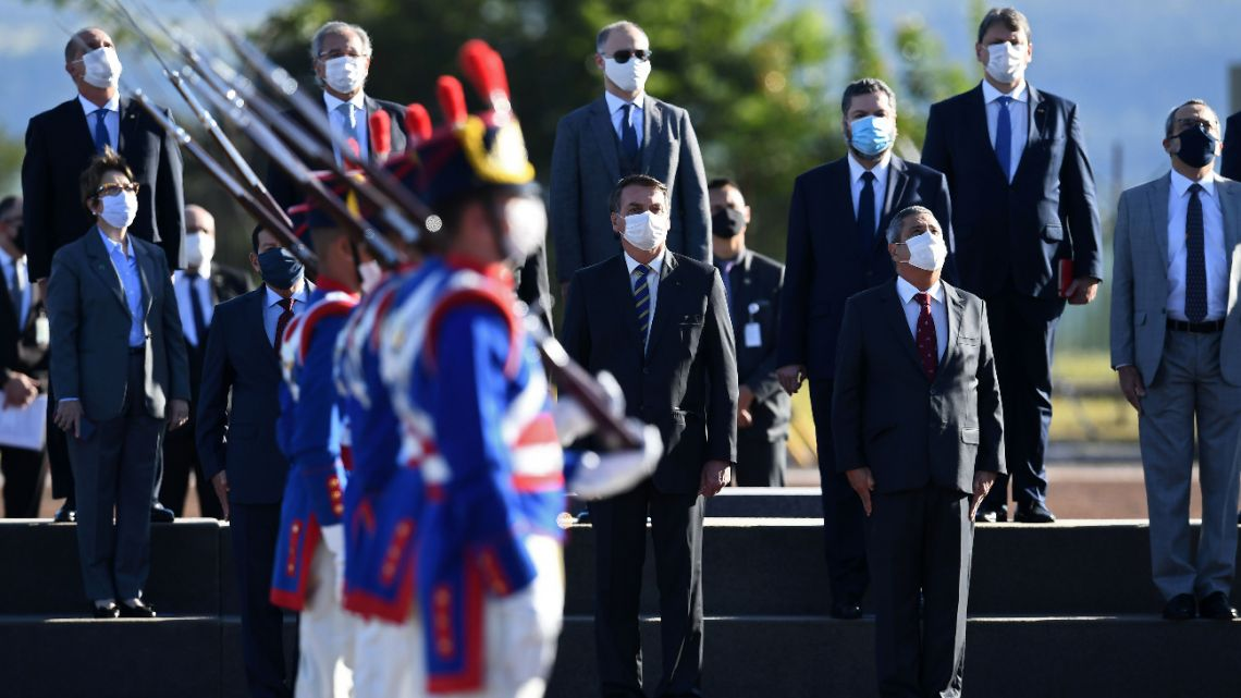 Brazilian President Jair Bolsonaro (C) and his Ministers attend the flag-raising ceremony before a ministerial meeting at the Alvorada Palace in Brasilia, on May 12, 2020, amid the new coronavirus pandemic.