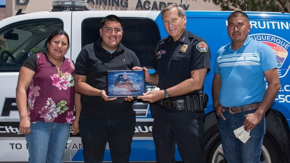 José junto a sus padres y uno de los oficiales que intervino en la investigación.