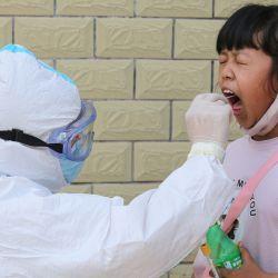 Un miembro del personal médico toma una muestra de hisopo de un niño para analizar el nuevo coronavirus COVID-19 en Jian en la provincia central de Jiangxi de China el 13 de mayo de 2020. (Foto de STR / AFP) / China OUT | Foto:AFP