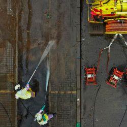 Los trabajadores lavan las calles antes de su desinfección, como medida preventiva contra la propagación del nuevo coronavirus, COVID-19, en el vecindario de Kennedy declarado en alerta naranja por ser una de las localidades con más casos en Bogotá, el 13 de mayo de 2020. ( Foto por Raúl ARBOLEDA / AFP) | Foto:AFP