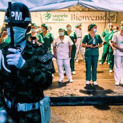 Las enfermeras observan cómo los soldados les rinden homenaje en el Día Internacional de la Enfermera, en la Clínica Sagrado Corazón en Medellín, Colombia, el 12 de mayo de 2020. - La pandemia de coronavirus ahora se ha cobrado más de 290,000 vidas en todo el mundo, según un recuento de fuentes oficiales de la AFP a las 2200 GMT del martes. (Foto de Joaquin SARMIENTO / AFP) | Foto:AFP