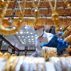 Un comerciante que usa una máscara facial, debido a la pandemia de coronavirus COVID-19, busca joyas en una tienda de joyas en el Dubai Gold Souk en el emirato del Golfo el 13 de mayo de 2020, a medida que los mercados vuelven a abrir en medio de una disminución de las restricciones de la pandemia. (Foto por Karim SAHIB / AFP)   Foto:AFP