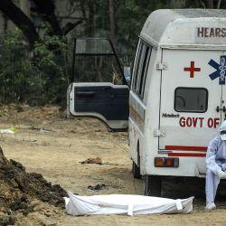 Un trabajador de la salud con equipo de protección se sienta en una ambulancia al lado del cadáver de una víctima que murió por el coronavirus COVID-19 antes del entierro en un cementerio en Nueva Delhi el 13 de mayo de 2020. (Foto por SAJJAD HUSSAIN / AFP)   Foto:AFP