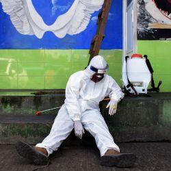 Un funcionario de la agencia de salud, visto junto a su dispensador de desinfectante, descansa junto a la entrada de un baño público mientras otros colegas (sin foto) realizan una prueba de reacción en cadena de la polimerasa (PCR) para el coronavirus COVID-19 en una estación de autobuses en Bandung, Java Occidental, el 13 de mayo de 2020. (Foto por TIMUR MATAHARI / AFP) | Foto:AFP