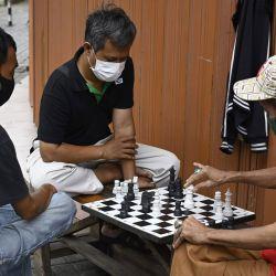 Hombres con mascarillas en medio de preocupaciones por el coronavirus COVID-19 juegan al ajedrez en Yakarta el 13 de mayo de 2020. (Foto de BAY ISMOYO / AFP) | Foto:AFP