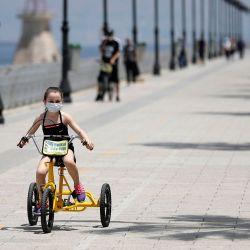 Una niña libanesa con una máscara facial monta una bicicleta en el corniche costero de Beirut el 13 de mayo de 2020. - El gabinete del Líbano anunció ayer un cierre nacional de cuatro días desde el miércoles por la noche después de un aumento en los casos de COVID-19 que el primer ministro Hassan Diab dijo amenazó la respuesta exitosa hasta ahora del país a la pandemia. (Foto por JOSEPH EID / AFP) | Foto:AFP