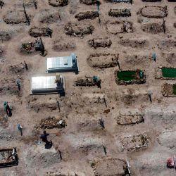 Imagen aérea que muestra a un trabajador (abajo, L) limpiando entre tumbas en el Cementerio Municipal # 13 en Tijuana, Estado de Baja California, México, el 12 de mayo de 2020, durante la pandemia del coronavirus COVID-19. - La pandemia de coronavirus ha cobrado más de 290,000 vidas en todo el mundo, según un recuento de fuentes oficiales de la AFP a las 2200 GMT del martes. (Foto de Guillermo Arias / AFP) | Foto:AFP