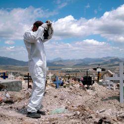 Un sepulturero se prepara para dos entierros COVID-19 en el Cementerio Municipal # 13 en Tijuana, Estado de Baja California, México, el 12 de mayo de 2020, durante la pandemia de coronavirus. - La pandemia de coronavirus ha cobrado más de 290,000 vidas en todo el mundo, según un recuento de fuentes oficiales de la AFP a las 2200 GMT del martes. (Foto de Guillermo Arias / AFP) | Foto:AFP