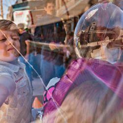 Un niño juega con globos exhibidos afuera de una tienda en el mercado principal de la ciudad de mayoría kurda de Qamishli, en la provincia de Hasakeh, en el noreste de Siria, el 12 de mayo de 2020, mientras la administración de la región kurda semiautónoma levanta las restricciones de bloqueo de COVID-19. (Foto por DELIL SOULEIMAN / AFP) | Foto:AFP