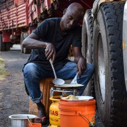 Una foto tomada el 5 de mayo de 2020 muestra a un conductor de camión preparando un Iftar, la cena que los musulmanes terminan con su ayuno diario en el Ramadán, junto a su camión, ya que ha estado esperando durante cinco días para que le hagan la prueba del coronavirus COVID-19 antes de ingresar. a Kenia como obligatorio para todos los conductores en Namanga, norte de Tanzania. (Foto por Filbert RWEYEMAMU / AFP) | Foto:AFP