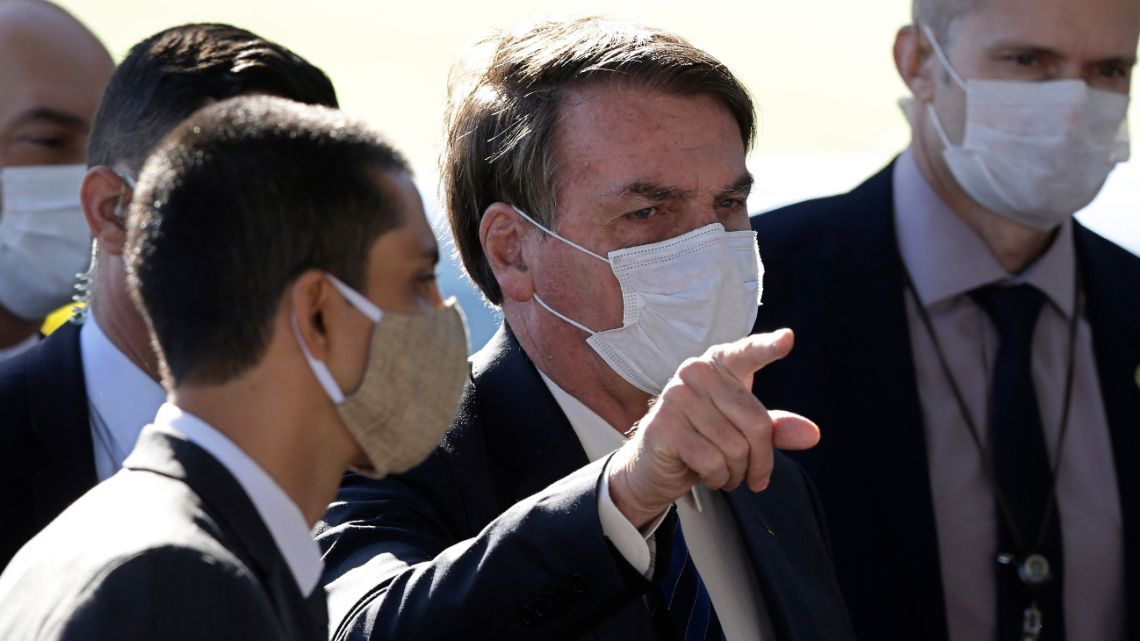 Brazil's President Jair Bolsonaro wears a face mask as he speaks to the press upon departure from the official residence of Alvorada palace in Brasilia, Brazil, Monday, May 11, 2020.