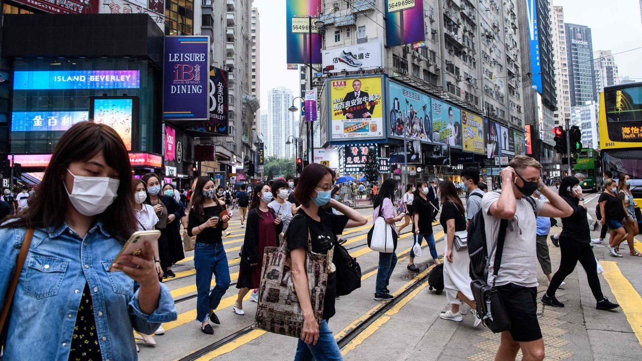 Los peatones usan mascarillas como medida de precaución contra el coronavirus COVID-19 mientras cruzan una carretera en Hong Kong el 13 de mayo de 2020. - Dos personas en Hong Kong dieron positivo por coronavirus, dijeron las autoridades el 13 de mayo, terminando un día de 24 días. No hubo nuevos casos locales que vieron a la ciudad comenzar a facilitar las regulaciones de distanciamiento social. (Foto por Anthony WALLACE / AFP)   Foto:AFP