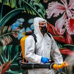 Un empleado que usa equipo de protección desinfecta un centro comercial como medida preventiva contra el coronavirus COVID-19 en Caxias do Sul, Brasil, el 13 de mayo de 2020. (Foto de SILVIO AVILA / AFP)   Foto:AFP