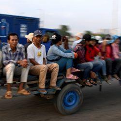La gente se sienta en un carro de motor que viaja por una calle en Phnom Penh el 14 de mayo de 2020. (Foto de TANG CHHIN Sothy / AFP)   Foto:AFP