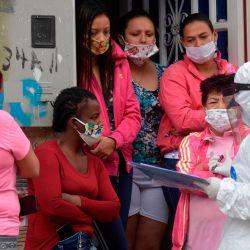 Los voluntarios entregan suministros de alimentos enviados por la oficina del alcalde de Bogotá a familias vulnerables en el vecindario Kennedy, en alerta naranja por alcanzar una de las tasas más altas de casos de coronavirus COVID-19, en Bogotá, el 13 de mayo de 2020. (Foto por Raúl ARBOLEDA / AFP )   Foto:AFP
