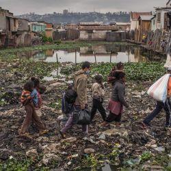 Safidy Andrianantenaina, uno de los cofundadores y cogerentes de la asociación Le Caméléon, camina en el distrito de Anjezika para distribuir paquetes de alimentos y máscaras faciales a sus residentes, en Antananarivo el 13 de mayo de 2020. - Le Caméléon, un humanitario independiente asociación fundada en 2017, ofrece tutoría a un centenar de niños en apuros en Anjezika, uno de los barrios más pobres y poco saludables de Antananarivo. Tras el cierre de la capital impuesto por las autoridades el 23 de marzo de 2020, muchas familias en Antananarivo perdieron sus empleos y se encontraron en una situación social aún más dramática. Desde el 21 de abril de 2020, los 15 voluntarios de Le Caméléon han decidido ayudar a las familias más pobres del distrito de Anjezika distribuyendo paquetes de alimentos o ropa en colaboración con otras ONG o movimientos de solidaridad malgaches como Solidarité Madagascar. (Foto por RIJASOLO / AFP)   Foto:AFP