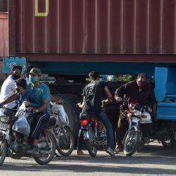 Los motociclistas se dirigen debajo de un camión contenedor que bloquea una calle después de que el gobierno alivió el bloqueo nacional impuesto como medida preventiva contra el coronavirus COVID-19, en Lahore el 14 de mayo de 2020. (Foto de ARIF ALI / AFP)   Foto:AFP