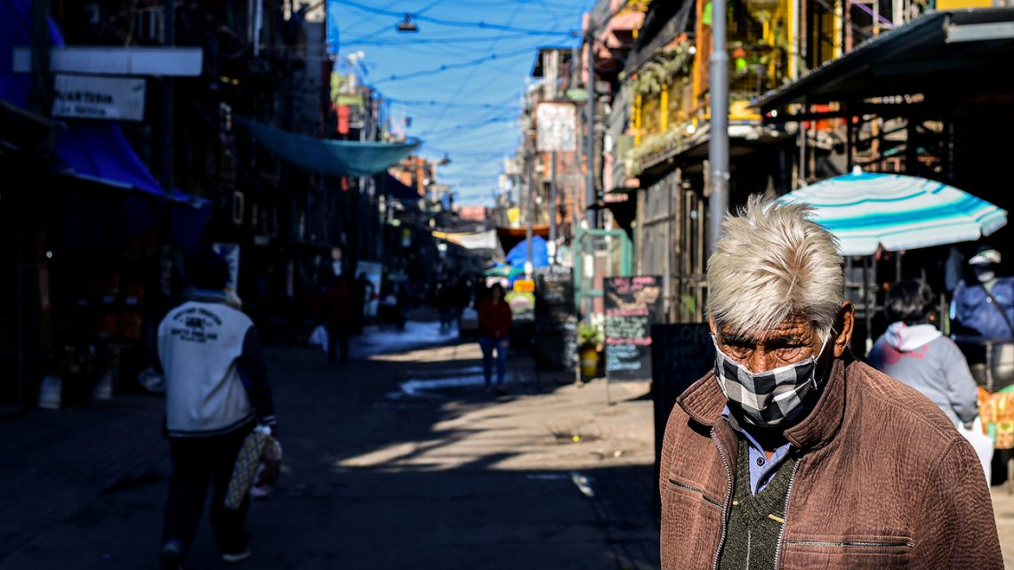 A man wears a face mask as he walks along a street in Villa 31 shantytown in downtown Buenos Aires