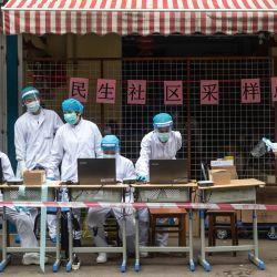 Los trabajadores médicos organizan una estación de prueba de coronavirus COVID-19 en una calle de Wuhan en la provincia central china de Hubei el 15 de mayo de 2020. - Las autoridades en la zona pandémica cero de Wuhan han ordenado pruebas masivas de COVID-19 para los 11 millones de residentes después de una nueva Grupo de casos surgió durante el fin de semana. (Foto por STR / AFP) / China OUT   Foto:AFP